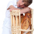 Little girl dressed in baker reposing on a bread bin - Stock Photo