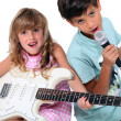 Little boy and girl playing musical instruments - Stock Photo