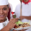 Young chief cook showing a salad dish — Stock Photo
