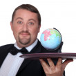 Waiter with a globe on a platter — Stock Photo