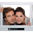 Couple posing in a television frame — Stock Photo