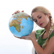Woman in green resting her head against a large globe — Stock Photo #10378480