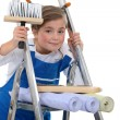 Little girl on a ladder holding a brush and wallpapers — Stock Photo