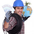 Electrician holding money and globe - Stock Photo