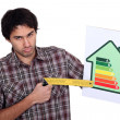 Stock Photo: Grumpy mpointing to lower end of energy efficiency rating scale with try square