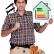 Stock Photo: Carpenter with calipers and energy rating guide