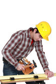 Young carpenter hammering down nail in plank — Stock Photo