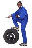 Cols bleus tenant croix robinet avec jambe reposant sur pneumatique — Photo