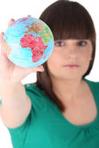 Teenage girl holding miniature globe — Stock Photo
