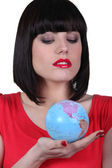 Woman holding the globe in her hand — Stock Photo