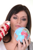 Woman spraying miniature globe — Stock Photo