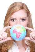 Young woman showing a little globe — Stock Photo