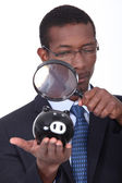 Black well dressed man watching a piggy bank with a magnifying glass — Stock Photo