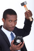 Man about to break open a piggy bank with a hammer — Stock Photo