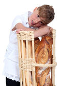 Little girl dressed in baker reposing on a bread bin — Stock Photo