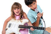 Little boy and girl playing musical instruments — Stock Photo
