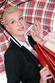 Blond woman shopping under the rain. — Stock Photo