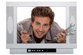 Young man with spanners poking his head through a mock up TV set — Stock Photo