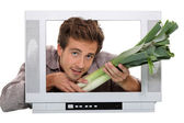 A man giving leeks through a screen — Stock Photo