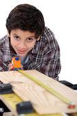 Boy carpenter measuring wood — Stock Photo