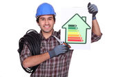 Electrician holding an energy consumption label — Stock Photo
