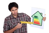 Grumpy man pointing to the lower end of an energy efficiency rating scale with a try square — Stock Photo
