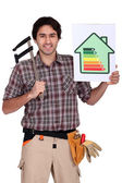Carpenter with calipers and energy rating guide — Stock Photo