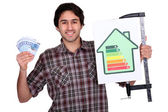 Man holding an energy consumption label and a lot of money in cash — Foto de Stock