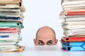 Man peeking through stacks of folders — Stock Photo