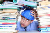Architect surrounded by piles of paperwork — Stock Photo
