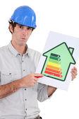 Artesano apuntando con el índice de consumo de energía de una casa — Foto de Stock