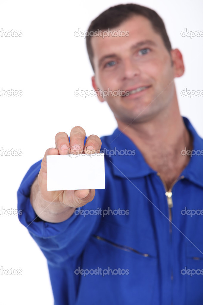 Man in blue overalls holding a business card left blank for your details — Stock Photo #10376933