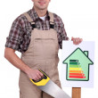 Builder holding up an energy efficiency rating sign — Stock Photo