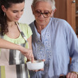 Stock Photo: Young womcooking with her grandmother