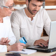 Stock Photo: Mhelping elderly family member shop on-line