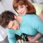 Woman embracing boy playing guitar — Stock Photo