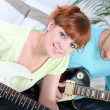 Couple sat playing the electric guitar — Stock Photo