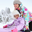 Mother and daughter playing in snow together — Stock Photo #10385781