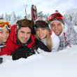 Stock Photo: Four young adults laying in snow