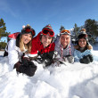 Four friends laying in snow — Stock Photo #10385823