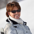 Happy middle-aged woman walking through the snow — Stock Photo