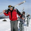 Young men with skis on shoulder - Stock Photo