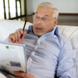 Stock Photo: Retiree playing crosswords