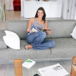 Woman sat reading magazine at home — Stock Photo