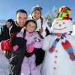 Family with a snowman - Stock Photo