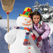 Girl next to snowman - Stock Photo