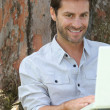 Man with laptop under tree — Stock Photo #10386405