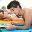 Couple on the beach with magazine — Stockfoto #10386615