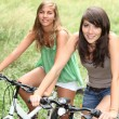 Two girls on a bicycle - Stock Photo