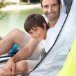 Stock Photo: Father and son campink by a lake